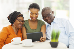 pretty young adult african girl with senior parents using tablet computer
