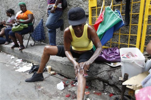 In this photo taken Feb. 15, 2011, a woman applies skin lightening cream to her legs as she sits on a curb in downtown Kingston, Jamaica. People around the world often try to alter their skin color, using tanning salons or dyes to darken it or other chemicals to lighten it. In the slums of Jamaica, doctors say the skin lightening phenomenon has reached dangerous proportions. (AP Photo/Caterina Werner)
